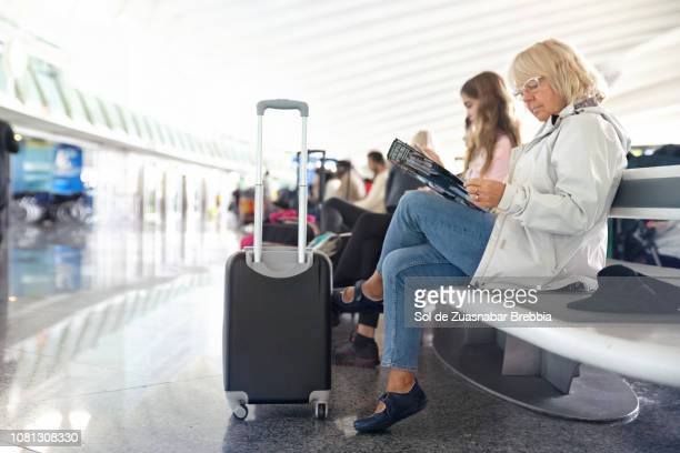 Senior woman sitting reading a magazine while waiting in a bright airport