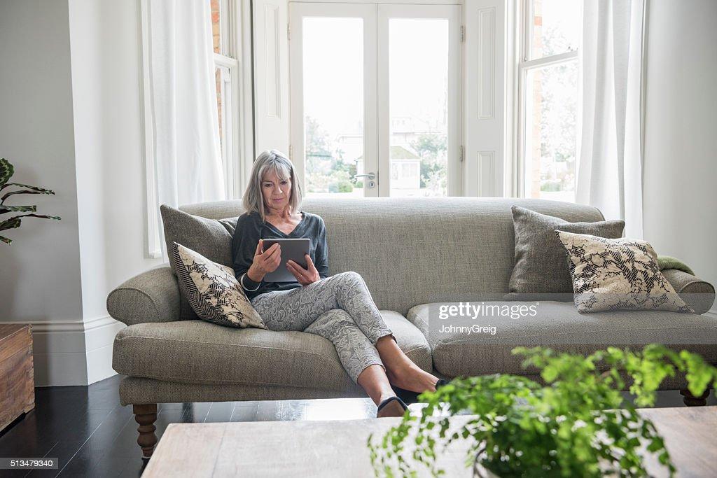 Sênior mulher sentada relaxante no sofá usando tabuleta digital : Foto de stock
