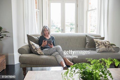 Senior donna seduta rilassante sul divano usando talea - Sesso sfrenato sul divano ...