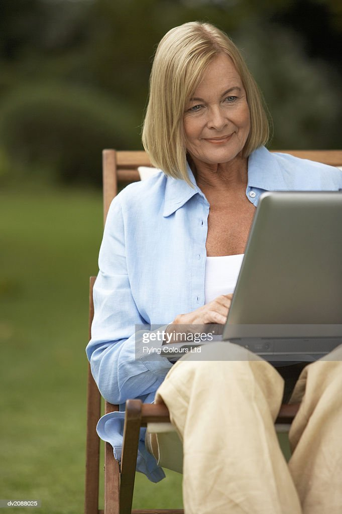 Senior Woman Sitting With a Laptop in Her Garden : Stock Photo