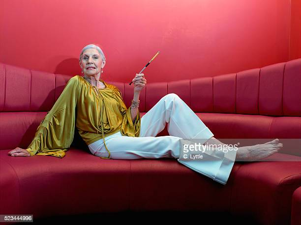 Senior Woman Sitting with Cigarette Holder on Red Sofa