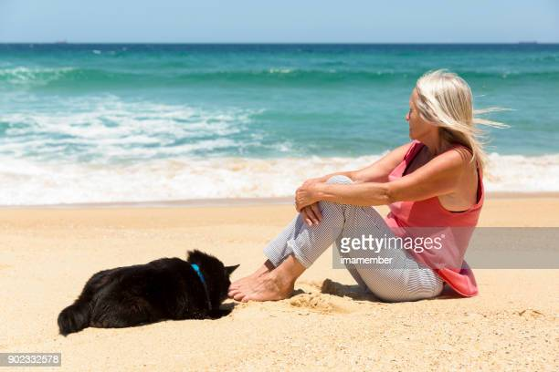 Senior woman sitting with dog on the beach and dreaming