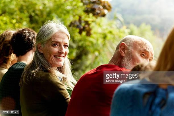 senior woman sitting with family at park - omkijken stockfoto's en -beelden