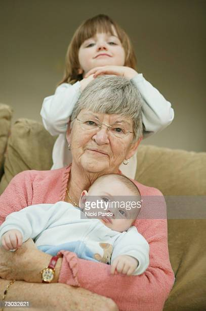 Senior woman sitting with grandchildren (0-4 years) on couch