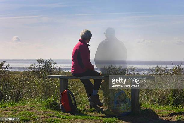 senior woman sitting with her ghosted partner - fading stock pictures, royalty-free photos & images