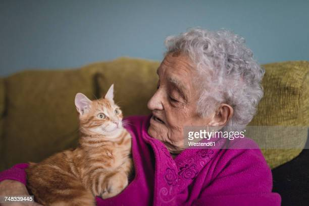 Senior woman sitting with tabby cat on the couch
