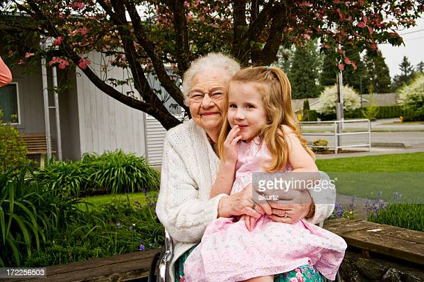 Senior woman sitting with young girl in her lap