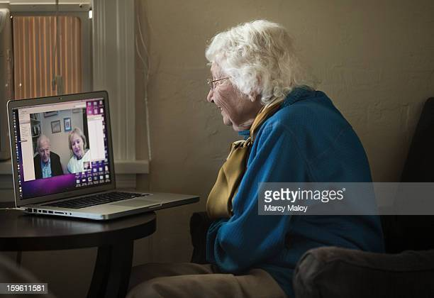 Senior woman Skypeing with friends on a laptop.