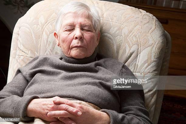 高齢者の女性の椅子付きの寝室