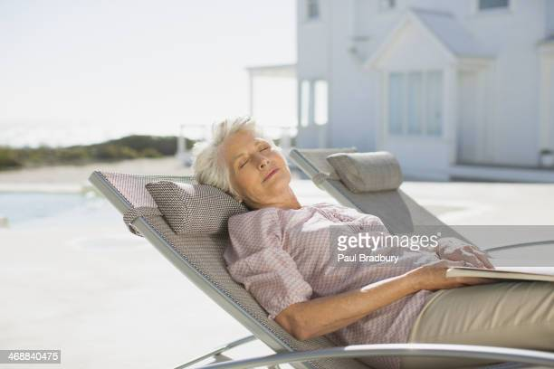 Senior woman sleeping on lounge chair at poolside