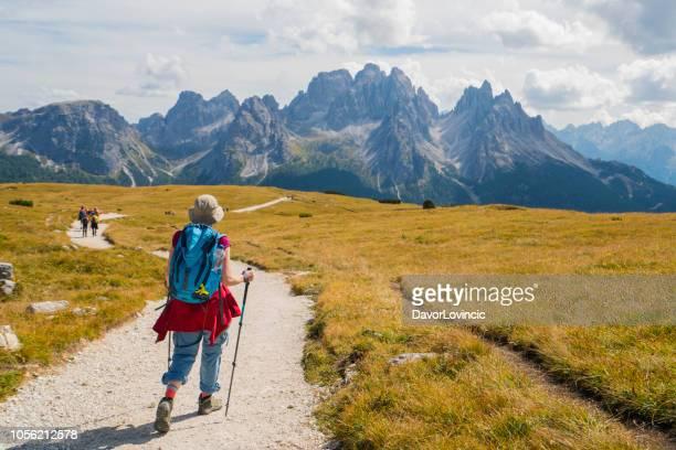 年配の女性マウント ピアナ、イタリアのドロミテの上ゆっくりと treking - トレチーメディラバレード ストックフォトと画像