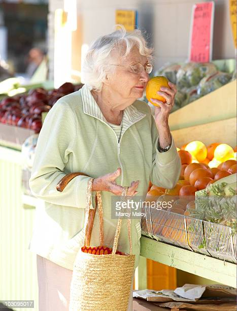 Senior woman smelling an orange at fruitstand.