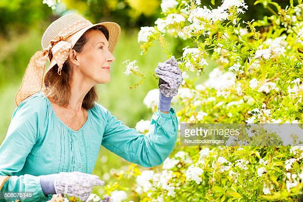 Senior Woman Smelling Flowers While Gardening In Garden