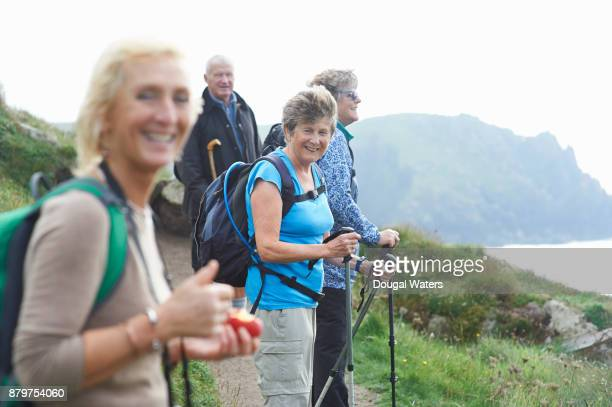 Senior woman smiles as part of a group hike.