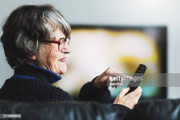 senior woman smiles as she uses tv remote control - one senior woman only stock pictures, royalty-free photos & images