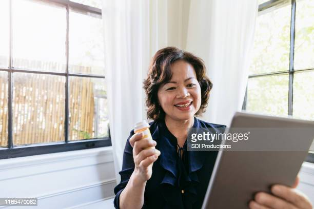 senior woman smiles at pharmacist on video conference - telemedicine stock photos and pictures