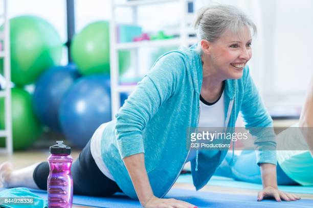 senior woman smiles during yoga pose at gym - lap body area stock photos and pictures