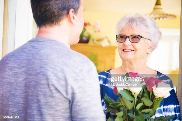 Senior woman smiles warmly at mature son bringing bouquet of roses