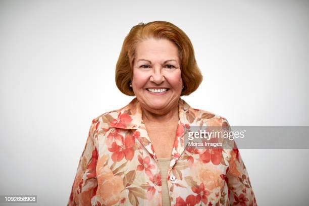 senior woman smiling against white background - seniore vrouwen stockfoto's en -beelden