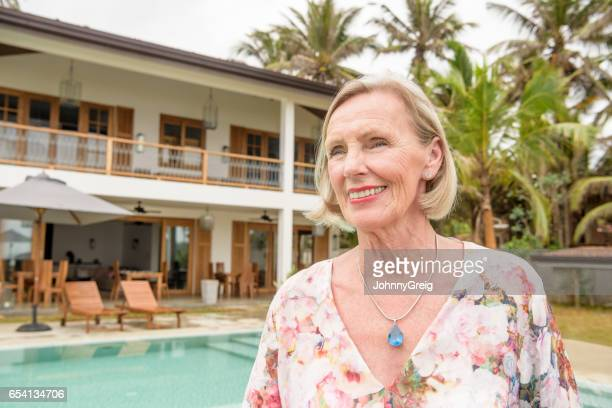Senior woman smiling and looking away with luxury villa in background