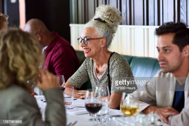 senior woman smiling and talking with friends in restaurant - glamour stock pictures, royalty-free photos & images