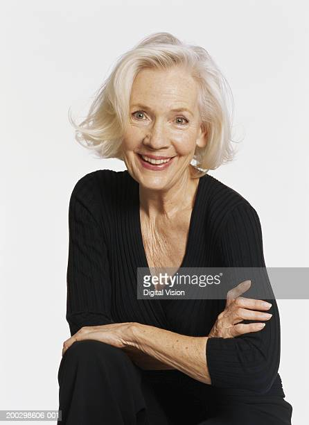 Senior woman smiling, arms crossed, portrait