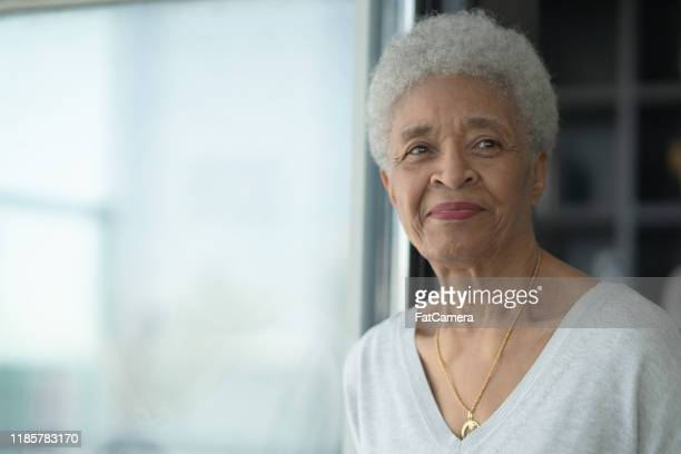 a senior woman smiling as she reflects stock photo - 50 59 years stock pictures, royalty-free photos & images
