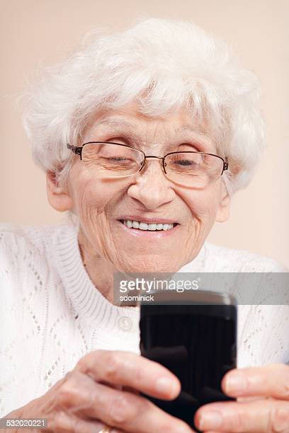 Senior Woman Smiling As She Texts on a Smart Phone