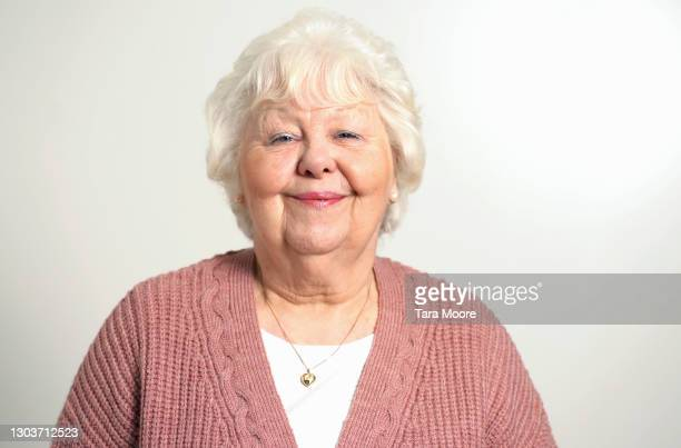 senior woman smiling at camera - 60 64 years stock pictures, royalty-free photos & images