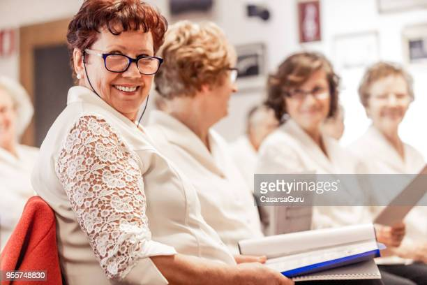 senior woman smiling at choir practice - choir stock pictures, royalty-free photos & images