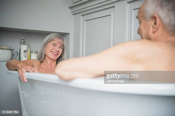 Senior woman smiling in bath with husband in foreground