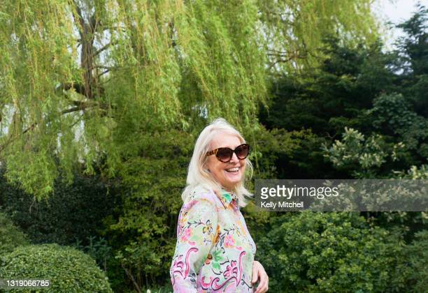 senior woman smiling laughing outside in a garden park - top garment stock pictures, royalty-free photos & images