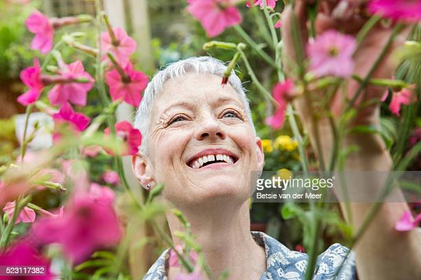 senior woman smiling, looking at flowering plant.