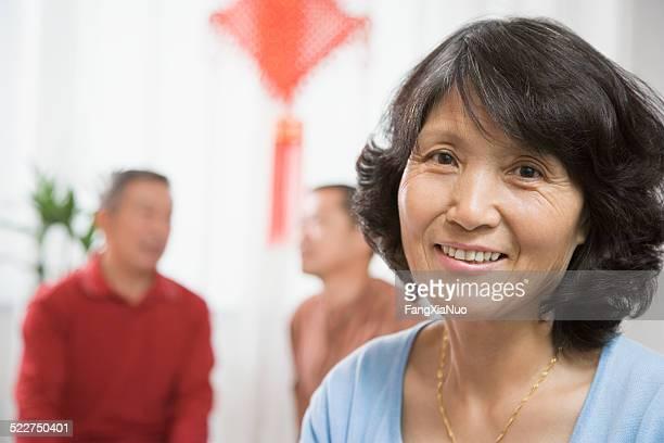 Femme âgée souriante, hommes en arrière-plan