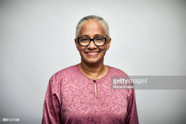 senior woman smiling over white background - 60 64 years stock pictures, royalty-free photos & images