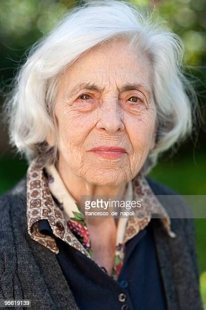 Senior woman smiling softly into the camera outdoors