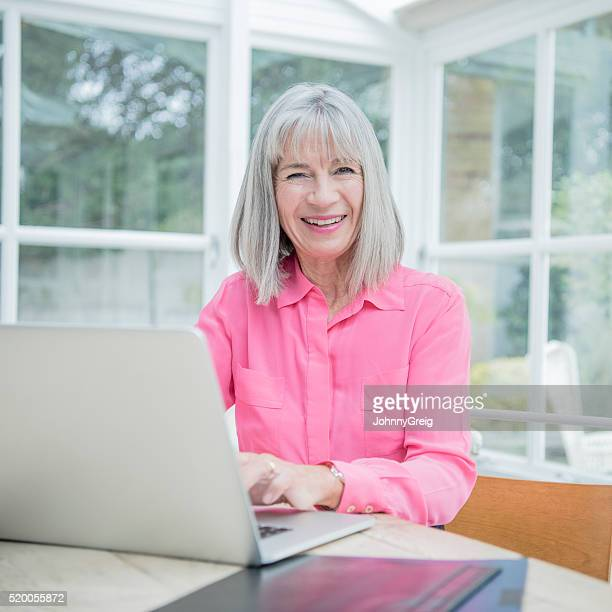 Senior woman smiling towards camer using laptop