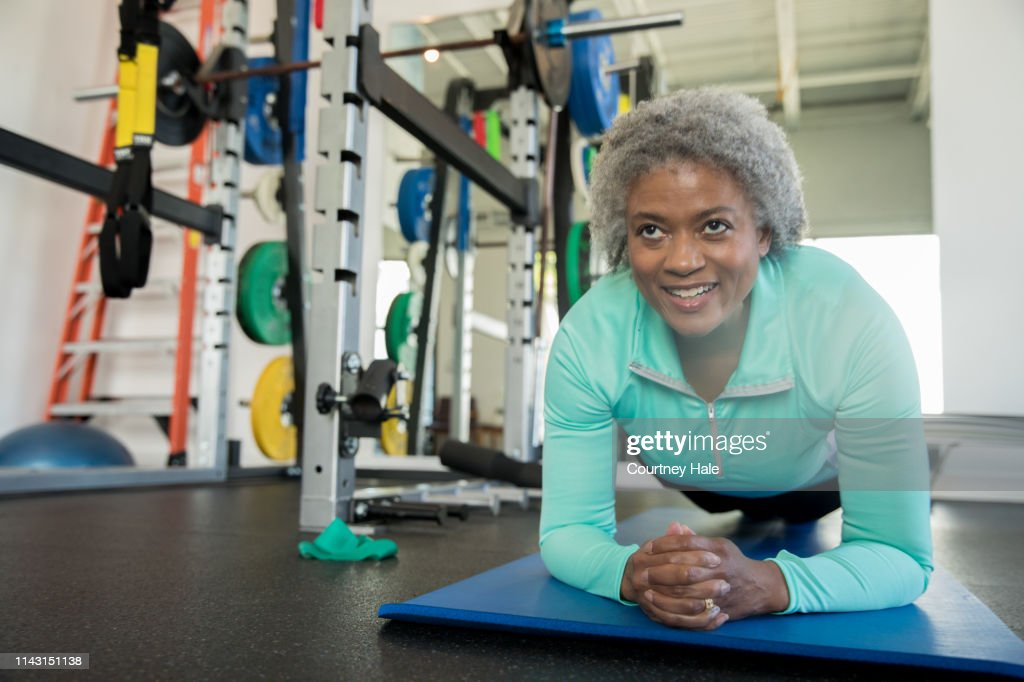 Senior woman smiling while doing a planking exercise in modern gym : Stock Photo