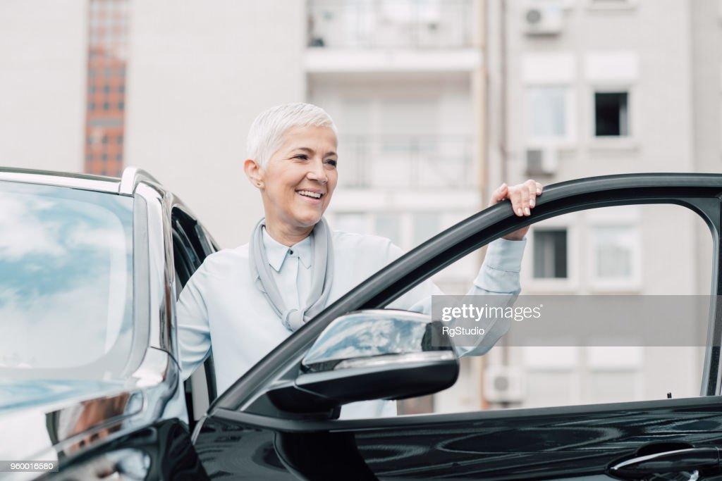 Ältere Frau Lächeln beim Betreten eines Autos : Stock-Foto
