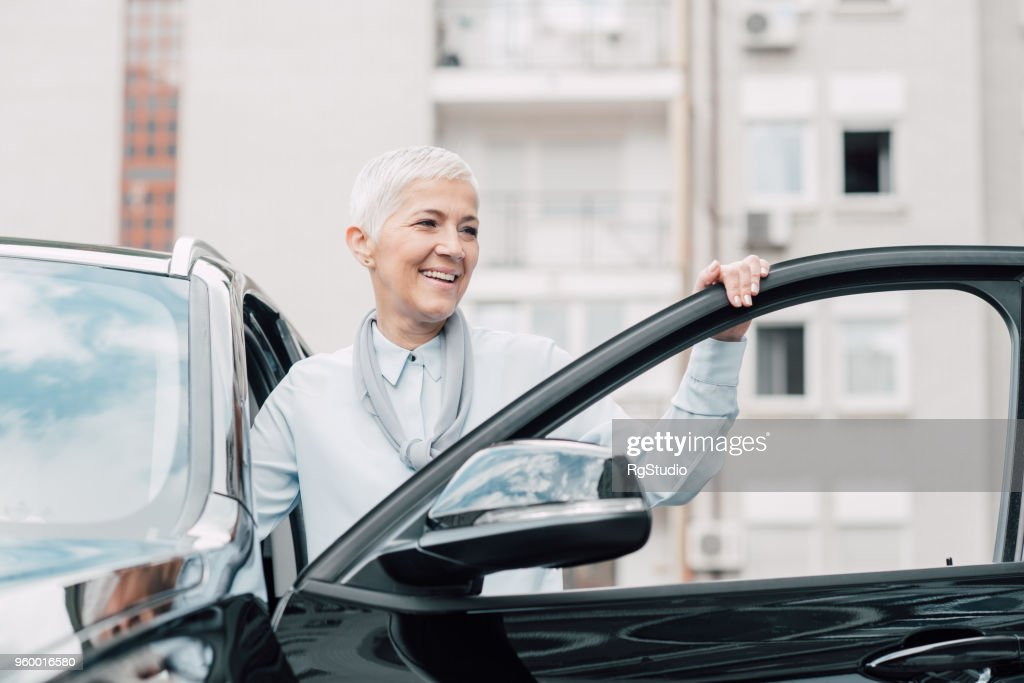 Senior woman smiling while entering a car : Stock Photo