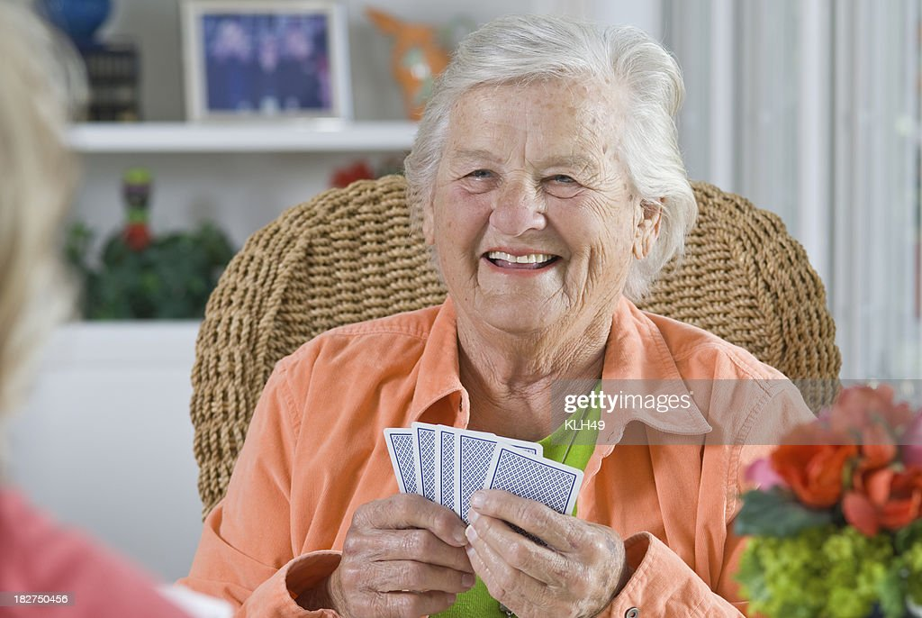 Senior Woman smiling while playing a card game : Stock Photo