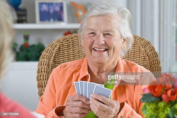 senior frau lächelnd, während sie eine card game - bridge card game stock-fotos und bilder
