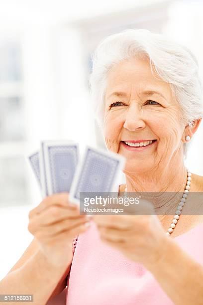 senior frau lächelnd während spielkarten - bridge card game stock-fotos und bilder