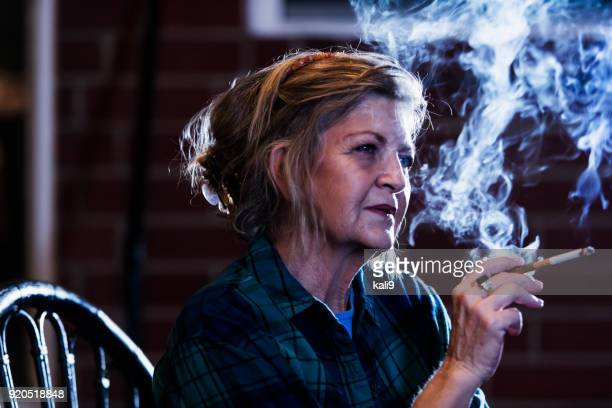 senior woman smoking a cigarette - unhealthy living stock pictures, royalty-free photos & images