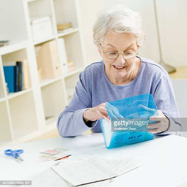 Senior woman sorting through coupons at home