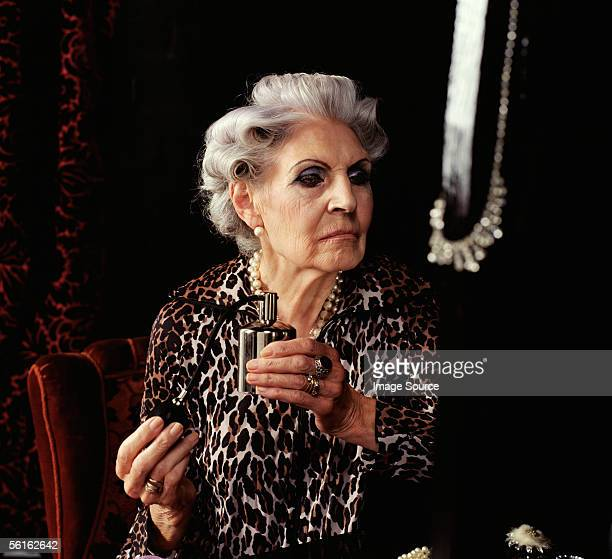 Senior woman spraying perfume