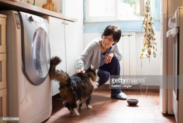 Senior woman squatting down to stroke her cat