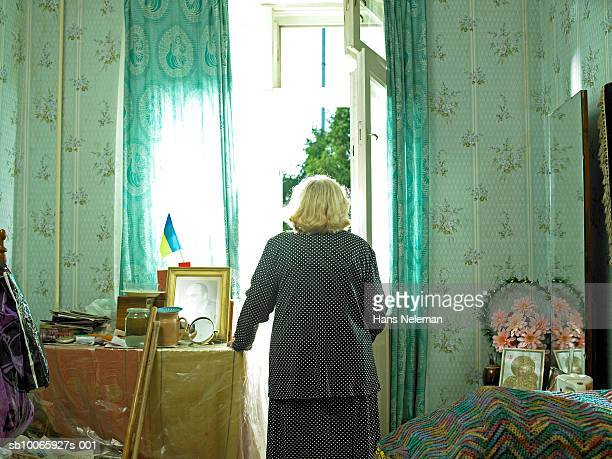 Senior woman standing at door, rear view