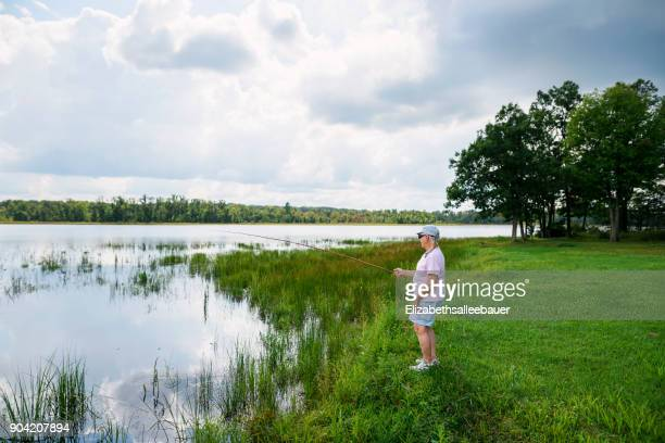 senior woman standing by a lake fishing - rivage photos et images de collection