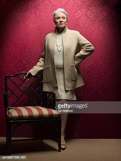 Senior woman standing by antique chair, portrait